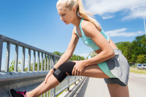Photo of a woman wearing a knee brace and resting during a jog to check her left knee.