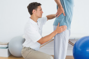 Photo of a physiotherapist assessing the lumbar spine of a man with back pain.
