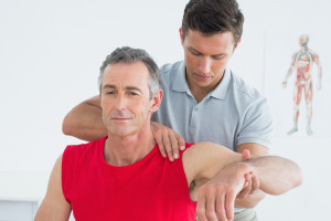 A physiotherapist assessing a man's shoulder range of motion.