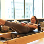 Smiling brunette woman doing arm exercises on a pilates reformer bed