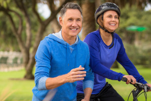 Photo of a mature man running and mature woman riding a bike together in a park.