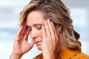 Photo of a woman suffering a headache, holding both of her hands to her temples.